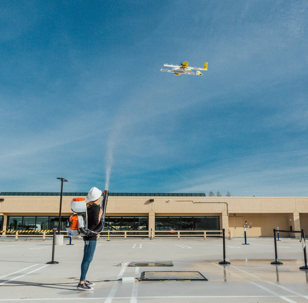 A person stands in a parking lot with a machine strapped to their back. The machine is attached to a hose which they're directing at a drone in a large blue sky.