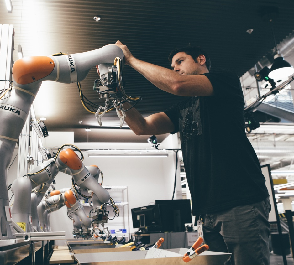 An engineer examines the first in a line of robotics arms.