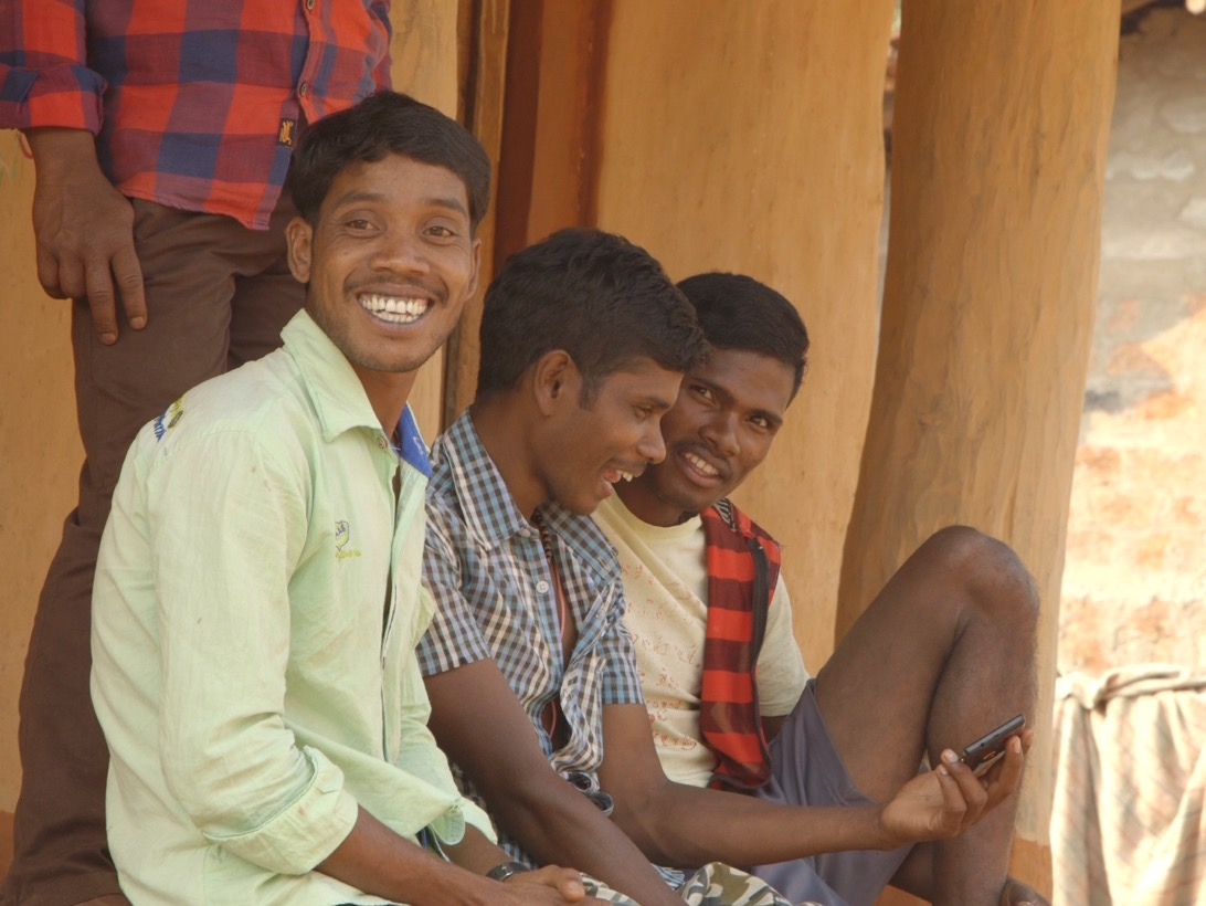 Smiling men in India look at cellphone.