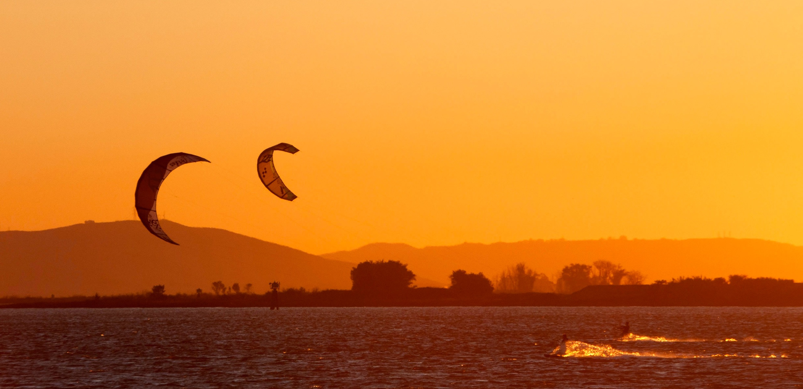 Kite surfers in river with beautiful orange sunset.